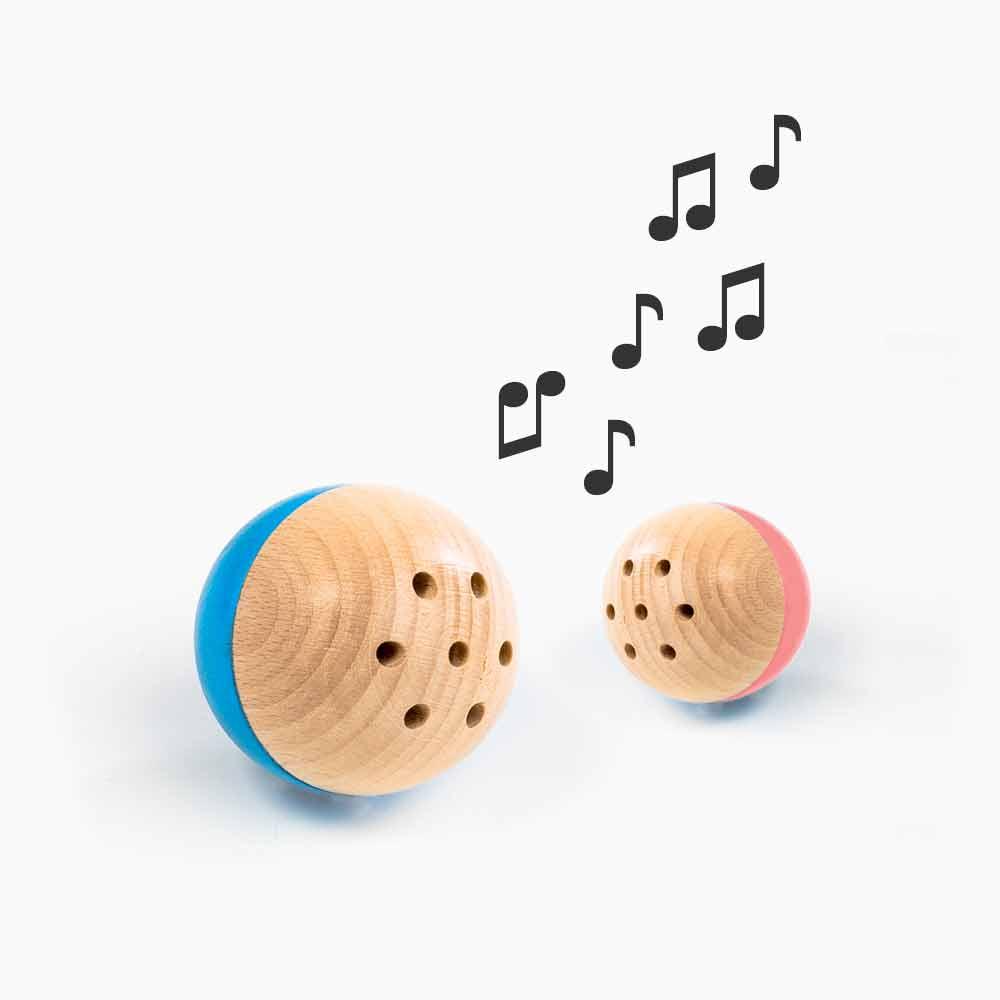 rewoodo Babyspielzeug Baelly in den Farben blau und rosa zusammen mit Noten die einen Ton andeuten, der aus dem Inneren des Balls durch ein Edelstahlglöckchen ertönt.