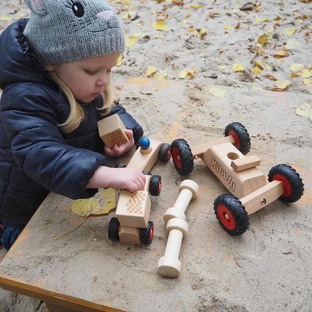 Mädchen spielt im Herbst mit rewoodo Holzspielzeug Kibbly und RibbleRace im Sandkasten