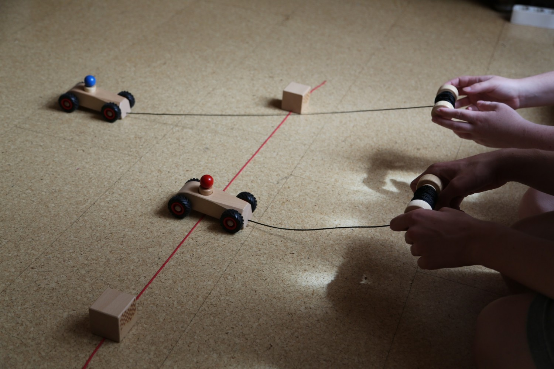2 Kinder spielen auf dem Boden mit dem RibbleRace von rewoodo. Holzspielzeug Rennen, inspiriert durch das bekannte Holzspielzeug Schneckenrennen mit Rennwagen.