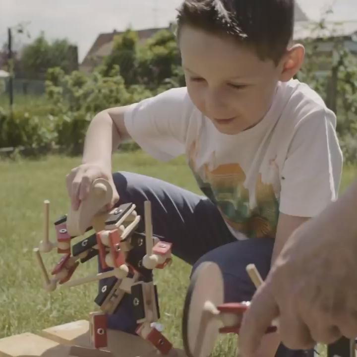 Kleiner Junge spielt mit den Helden aus Holz und seinem Vater im Sommer im Garten - Outdoor Holzspielzeug